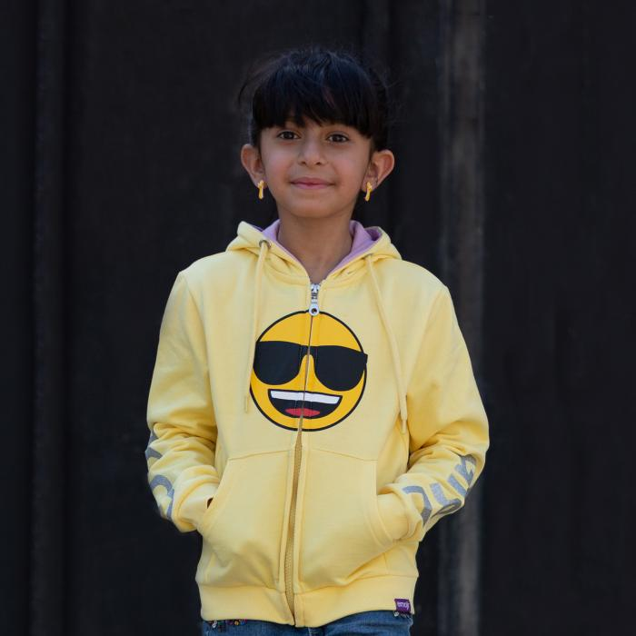 A young girl standing in front of a dark wall wearing a yellow sweatshirt with a smiley face in the middle of the chest. She is smiling and has her hands in her pockets.