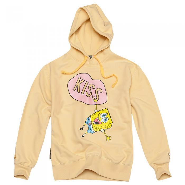 A yellow hoodie displayed in front of a white background. In the middle of the hoodie is a yellow cartoon character hanging off an illustration of pink lips that have the word kiss written across them.