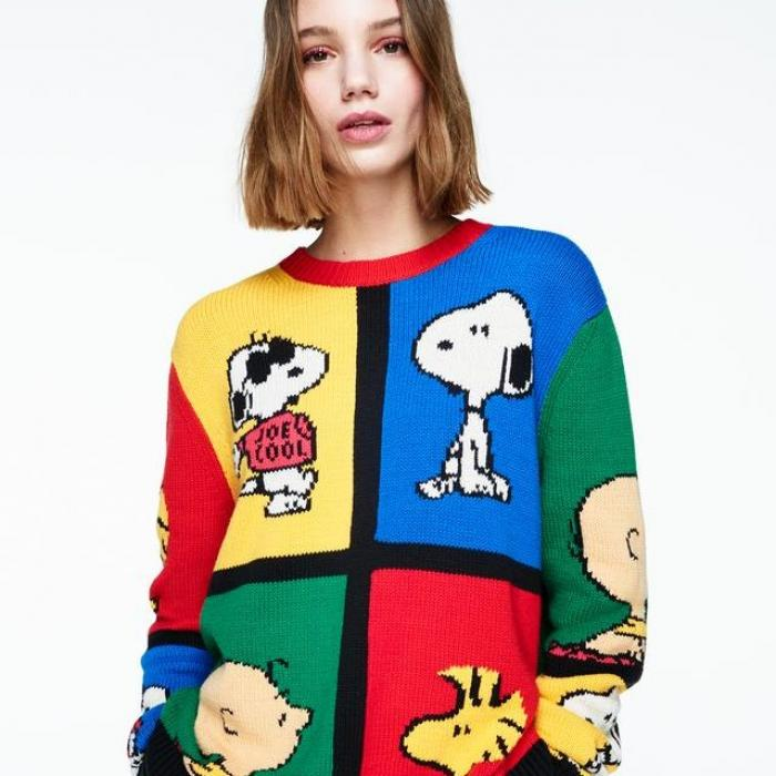 A young woman wearing a colourful sweater. The sweater has a large blue, red, yellow, and green square. Each square has a show character.
