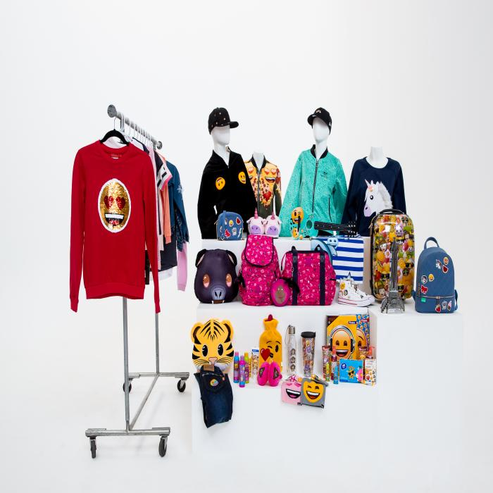 Merchandise displayed on a white surface. Some clothes are on a clothing rack and others are on white platforms.