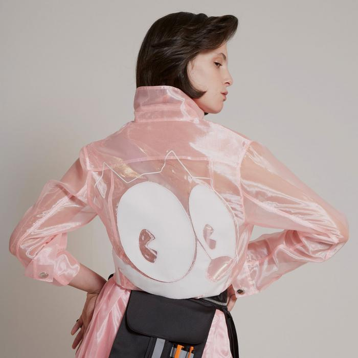 A shot of a woman's back wearing a light pink robe with big white eyes in them middle. She has a black fanny pack around her waist.