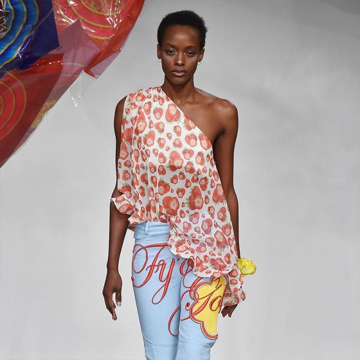 A female model walking down a runway wearing light blue pants and an off-shoulder white blouse with an orange print.
