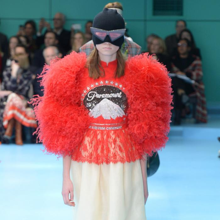 A female model walking on a runway wearing a puffy red top, a white shirt and a black mask.