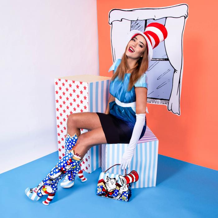 A woman, wearing a blue, black and white outfit is sitting on a colourful box. She is wearing boots and a purse with a busy, blue, red and white pattern.