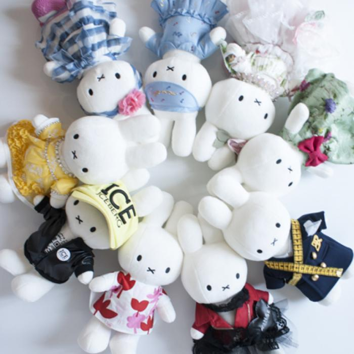 A bunch of white rabbit toys laying flat on a white surface. Each rabbit is wearing a different outfit.