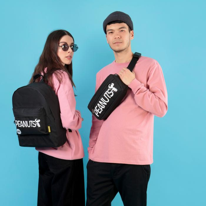 A man and a woman, wearing pink shirts and black bottoms are standing in front of a light blue wall. The woman is wearing sunglasses and a black backpack. The man is wearing a black fanny pack.