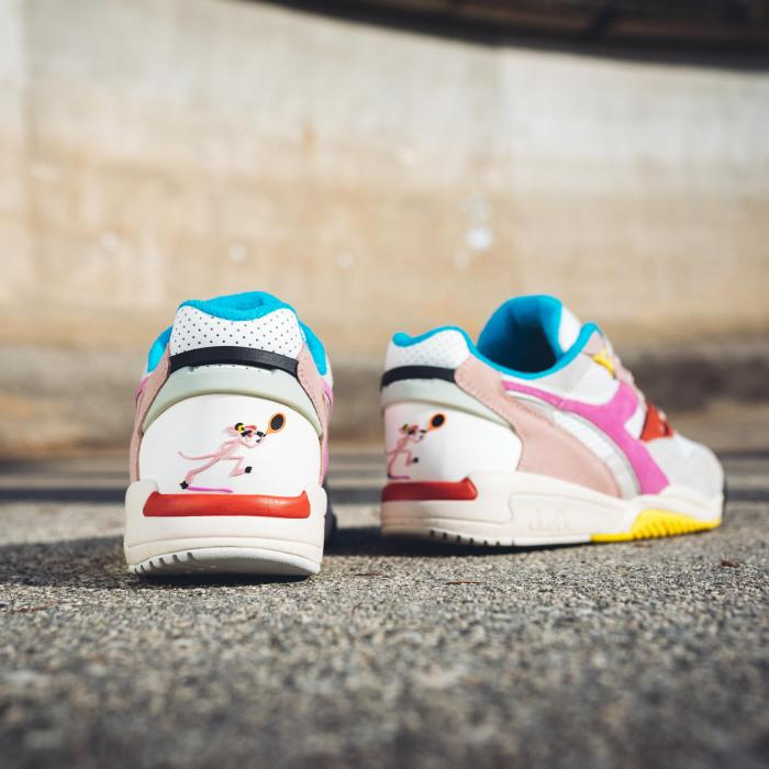 A view from the back of white sneakers on a cement floor. The shoes have pink, blue, red and yellow details.