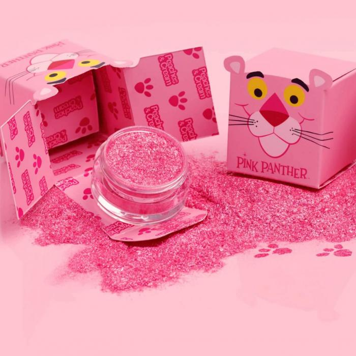 Two pink boxes with a panther face sitting on a table. One box is open and knocked over with pink glitter everywhere. The image is overlaid by a white Metro Goldwyn Mayer logo.