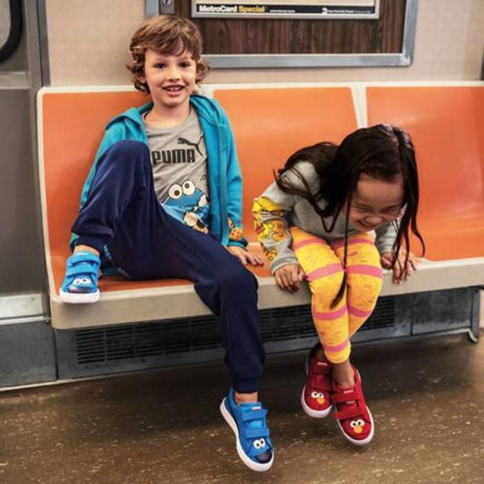A young boy and girl sitting inside a train and laughing.