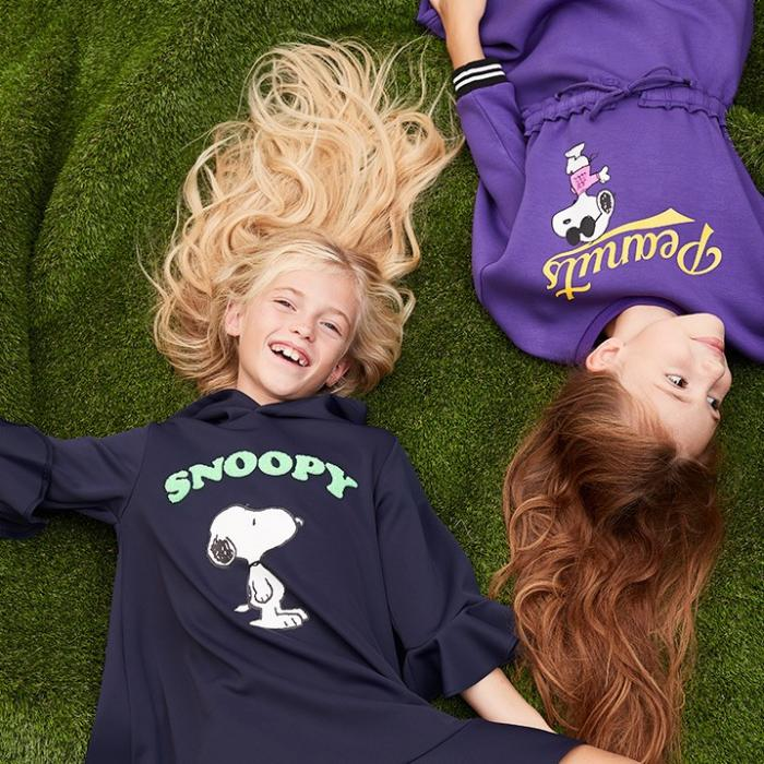 A bird's eye view of two young girls laying on the grass laughing. The girl with blonde hair is wearing a navy blue dress and the girl with red hair is wearing a purple dress.