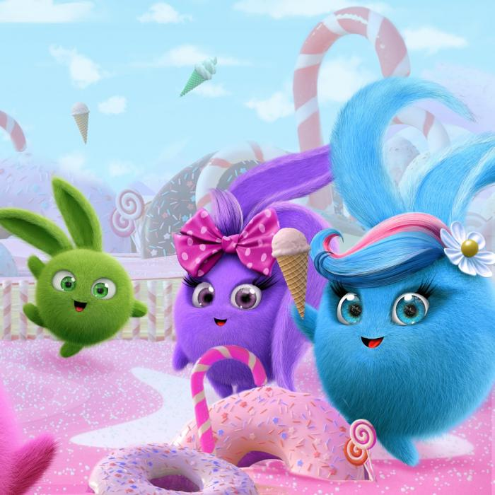 Three fluffy, round bunnies standing on a pink surface with doughnuts on the ground.