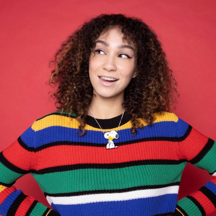 A woman with curly brown hair is looking off to the side with her hands on her waist. She is wearing a colourful, striped sweater and standing in front of a pink background.