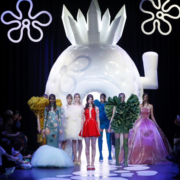 A group of models standing in the middle of a runway, wearing colourful outfits. Behind them is a large, white structure.
