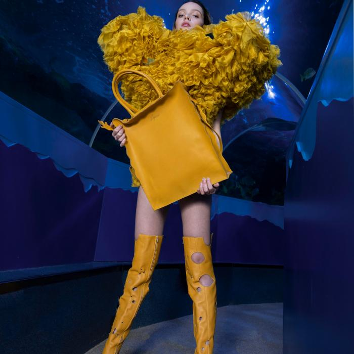 A female model standing in front of a dark blue backdrop. She is wearing yellow boots, a puffy yellow dress and holding a big yellow purse.