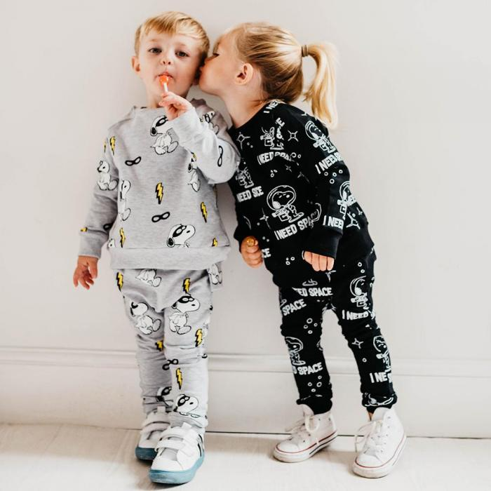 A blonde, pre-school girl is leaning over and kissing a blonde, pre-school boy on the cheek. The boy is wearing a grey top, grey sweatpants and sucking on a lollipop. The girl is wearing black sweatpants and a black top.