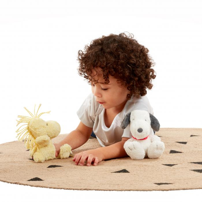 A preschool kid laying on his stomach playing with two toys. He is on a brown rug and in front on a white background.