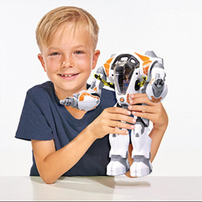 A blonde boy, wearing a navy blue shirt, is smiling and holding a robot in his hands. There is a white background behind him.