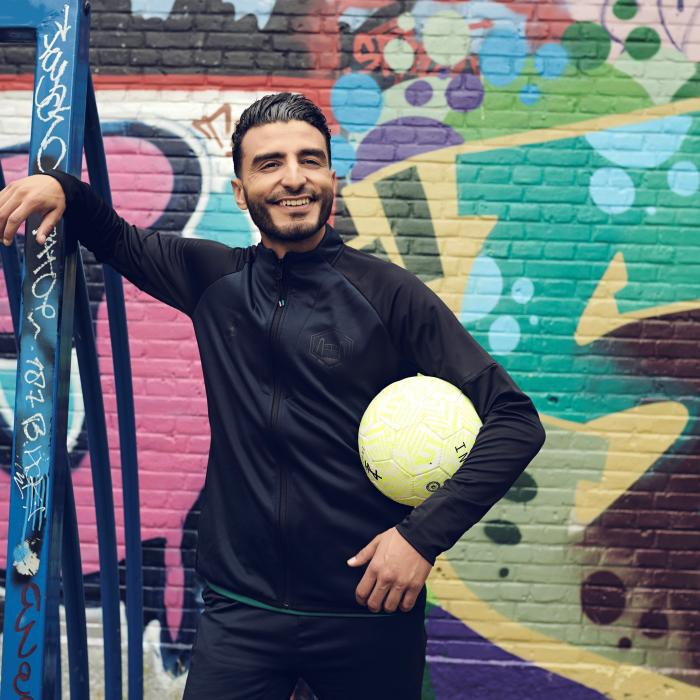 A man in a black shirt is smiling and leaning against a railing. He is holding a yellow soccer ball underneath his armpit and standing in front of a graffiti wall.