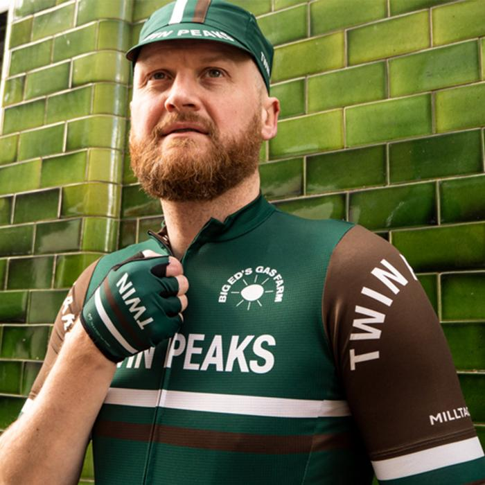 A close-up shot of a male cyclist wearing a green and brown cycling uniform.
