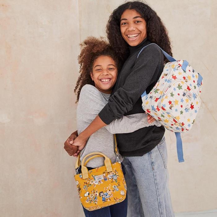 Two young girls, wearing colourful backpacks, hugging each other and smiling.