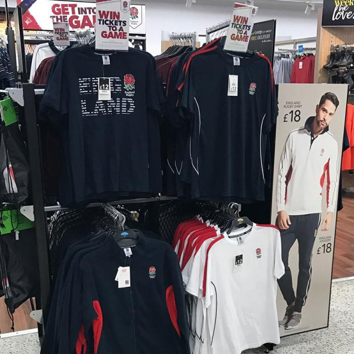 Men's rugby shirts hanging on display in a clothing store.