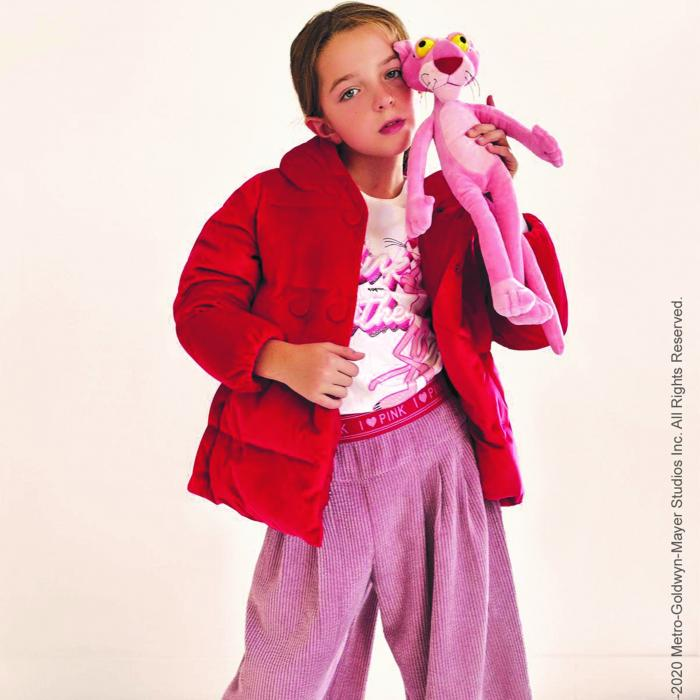 A young girl, wearing pink pants and a red jacket is standing and holding a plush, pink panther toy against her face.
