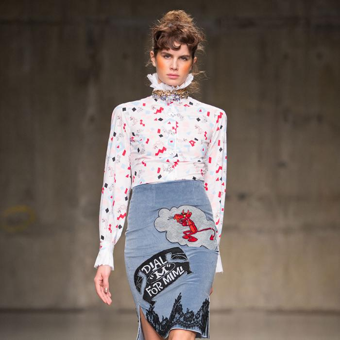 A model walking down a runway, wearing a white blouse with red and blue pattern and a light blue skirt.